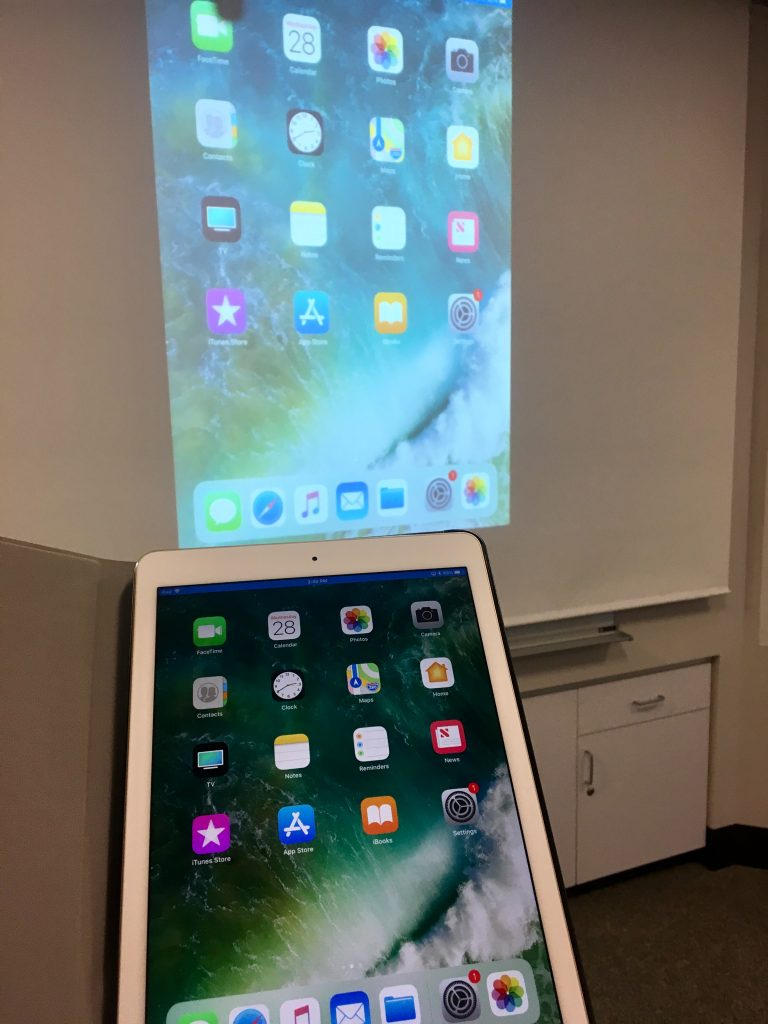 An iPad show shown sharing its screen through a projector