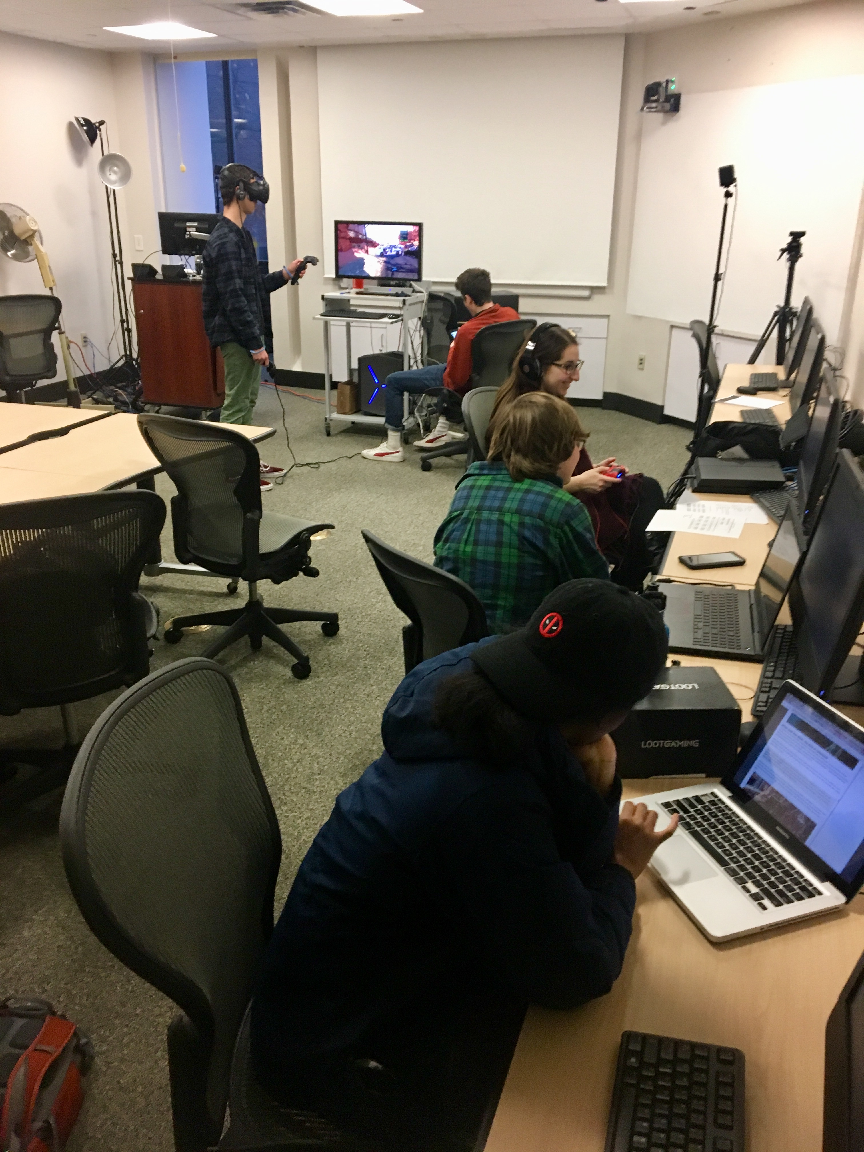 A room of students use virtual reality headsets in a classroom